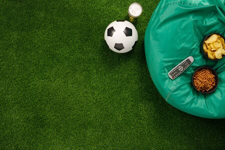 Soccer ball on a green field and ottoman for a fan with snacks and a TV remote control. View from above. flat lay. The concept of football matches.