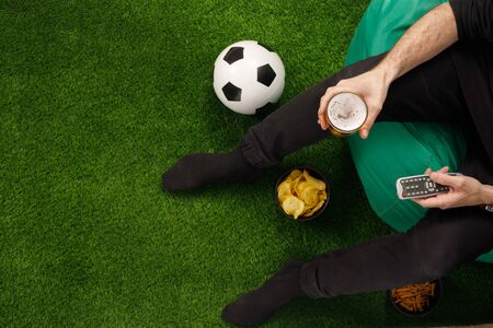 A man sits at the TV and watches a football match. Sneki TV remote. Soccer ball. View from above. Copy space. Banque d'images - 134724617