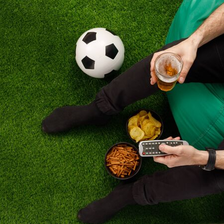 A man sits at the TV and watches a football match. Sneki TV remote. Soccer ball. View from above. Copy space. Banque d'images - 134724619