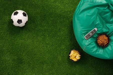 Soccer ball on a green field and ottoman for a fan with snacks and a TV remote control. View from above. flat lay. The concept of football matches. Banque d'images - 134724620