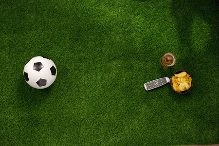 Soccer ball on a green field and ottoman for a fan with snacks and a TV remote control. flat lay. The concept of football matches.