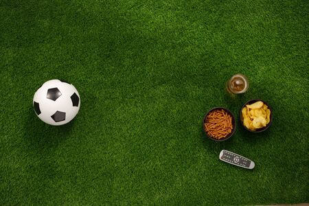 Soccer ball on a green field and ottoman for a fan with snacks and a TV remote control. flat lay. The concept of football matches. Banque d'images - 134724627