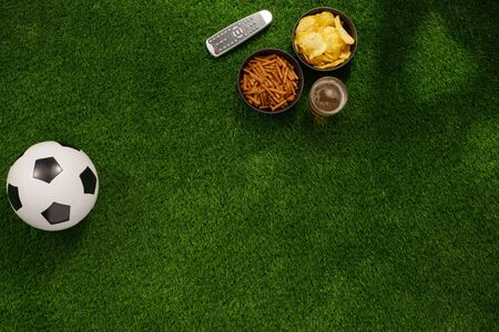 Soccer ball on a green field and ottoman for a fan with snacks and a TV remote control. flat lay. The concept of football matches. Banque d'images - 134724632