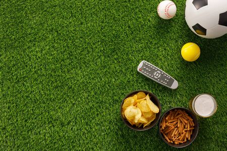 Soccer ball on a green field and ottoman for a fan with snacks and a TV remote control. flat lay. The concept of football matches. Banque d'images - 134724633