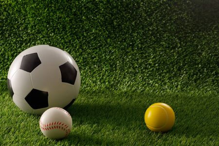 Soccer and baseball balls on a green field. The concept of football matches. Copy space. Close-up.
