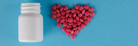 Packing pills. Heart shape made of pills. Pills spilling out of a jar on a blue background.