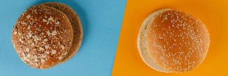 Rye and classic bun empty isolated. American food classic rye round burger bread isolated on blue and orange background. Two different fried hamburger buns. Close-up. Versus.