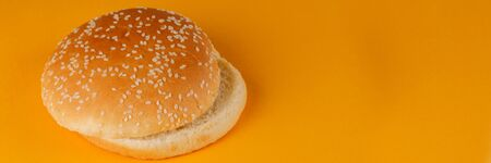 Burger bun empty isolated. American food classic round burger bread isolated on a orange background. Grilled burger bun top.Close-up.