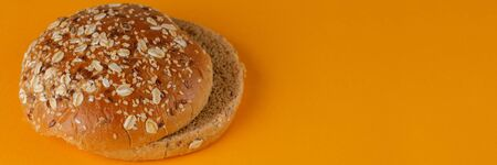 Rye bun empty isolated. American food classic rye round burger bread isolated on orange background. Grilled burger bun top. Close-up.