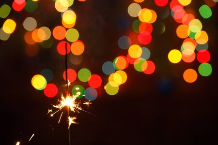 beautiful sparklers on the background of a garland. beautiful holiday card for the New Year. Happy.