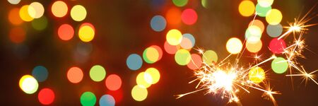 beautiful sparklers on the background of a garland. beautiful banner for the New Year. Happy.