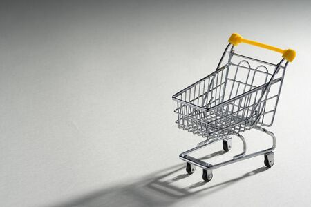 Shopaholic. Buyer. Shopping concept. Close-up. An isolated trolley and shopping basket on a ivory background bisected. Macro. Reklamní fotografie