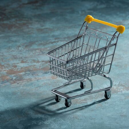 Shopaholic. Buyer. Shopping concept. Close-up. An isolated trolley and shopping basket on a textural navy blue background. Macro.