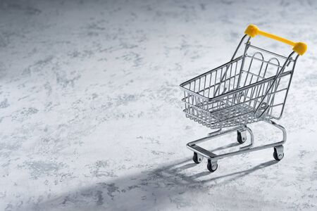 Shopaholic. Buyer. Shopping concept. Close-up. An isolated trolley and shopping basket on a white background bisected. Macro. Reklamní fotografie