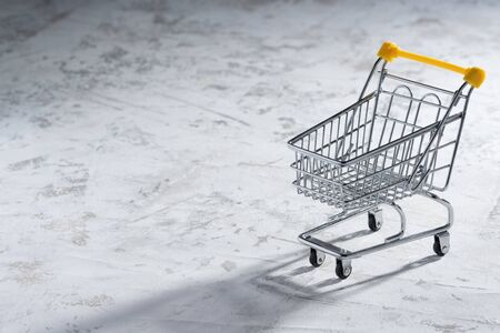 Shopaholic. Buyer. Shopping concept. Close-up. An isolated trolley and shopping basket on a white background bisected. Macro.