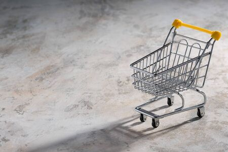 Shopaholic. Buyer. Shopping concept. Close-up. An isolated trolley and shopping basket on a beige background bisected. Macro.