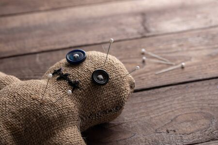 Voodoo doll on a wooden background with dramatic lighting. The concept of witchcraft and black art. Burlap doll on a wooden background. Pierce with maces.