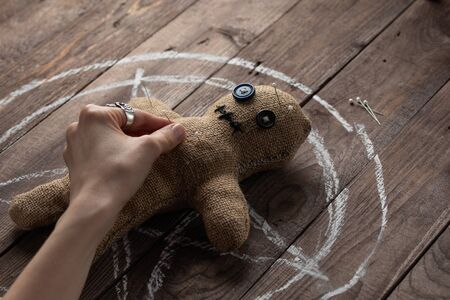 Voodoo doll on a wooden background with dramatic lighting. The concept of witchcraft and black art and the occult. Burlap doll on the background of a drawn star. Hand sticking pins into a doll. Copy space.