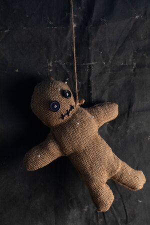 Voodoo doll on a black background with dramatic lighting. The concept of witchcraft and black art and the occult. Burlap doll. Copy space.