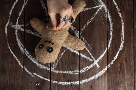 Muñeco vudú sobre un fondo de madera con una iluminación espectacular. El concepto de brujería y arte negro y lo oculto. Muñeca de arpillera en el fondo de una estrella dibujada. Colocar alfileres a mano en una muñeca. Copie el espacio.