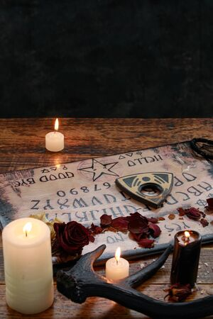 Mystic ritual with Ouija and candles. Devil's board concept, black magic or fortune telling rite with occult and esoteric symbols. Occultism. Stock Photo