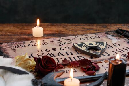 Mystic ritual with Ouija and candles. Devil's board concept, black magic or fortune telling rite with occult and esoteric symbols. Occultism.