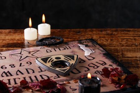 Spiritual board ouija with candles close-up. Mystical ritual of calling dead spirits. Macro. Occultism.