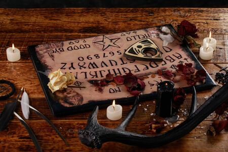 Talking board and planchette, also known as board, used for communicating with the dead and other spirits. The atmosphere of black art with candles and horns of the animal.