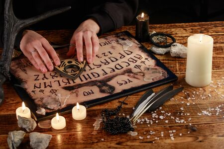 Hands on the devil's board. Session of calling spirits. Occult sciences, the atmosphere of black magic. Occultism.