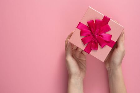 Valentines Day celebration concept. A nice gift from a loved one. Box with a bow in female hands on a delicate pink background. Copy space.