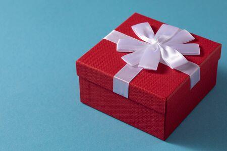 Valentinstag Feier Konzept. Ein schönes Geschenk von einem geliebten Menschen. Box mit einer Schleife auf einem sanften blauen Hintergrund. Platz kopieren. Flach liegen.