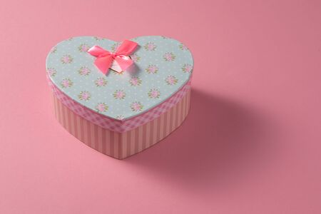 Valentines Day celebration concept. A nice gift from a loved one. Box with a bow on a delicate pink background. Copy space. Flat lay. 版權商用圖片