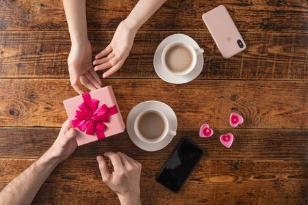 Valentines Day celebration concept. A nice gift for your loved one. Hands of man and woman with coffee mugs on a wooden table background. Copy space. Flat lay. 版權商用圖片