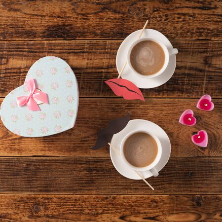 Valentines Day celebration concept. A nice gift for your loved one. Coffee mugs and gift on a wooden table background. Copy space. 版權商用圖片