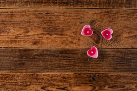 Valentines day burning candles in the form of hearts on a wooden table. Valentines Day celebration concept. 版權商用圖片