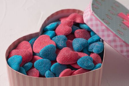 Sweet gift in a box in the form of a heart on a textural background. Marmalade in sugar blue and rose in the form of hearts Valentines day holiday concept.