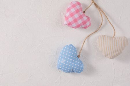 Hearts made of textile on a craft rope arranged together on a textured background. Valentine's day concept. Close-up. Foto de archivo - 140887422