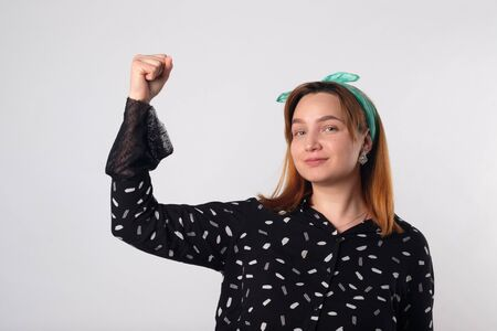Girl power concept. Young woman showing her arm for feminine and independent strength. Studio shot.