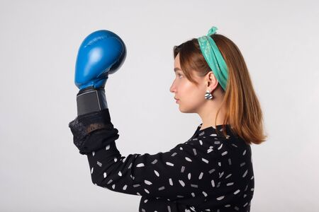 Girl power concept. Confident young woman isolated on gray wall background. Feminine and independent strength.Girl in boxing gloves. Female power concept. Boxing gloves on a girl. Close-up. Foto de archivo