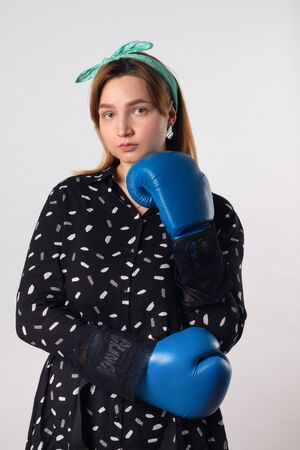 Girl power concept. Confident young woman isolated on gray wall background. Feminine and independent strength.Girl in boxing gloves. Studio shot. Foto de archivo