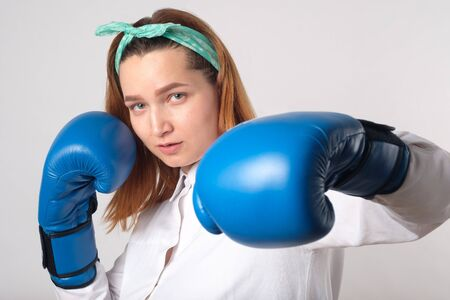 Girl power concept. Confident young woman isolated on a gray wall background. Female and independent power. The girl raises her hand in a boxing glove to strike. Studio shot. Foto de archivo