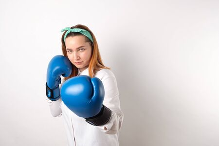 Girl power concept. Confident young woman isolated on a gray wall background. Female and independent power. The girl raises her hand in a boxing glove to strike. Studio shot. Banco de Imagens