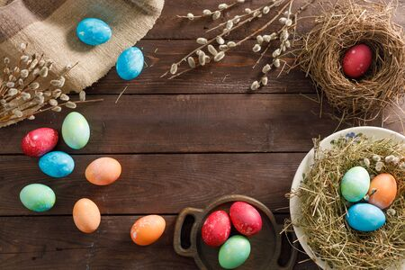 Still life many colorful easter eggs on a wooden background. Rustic. Decoration from natural fabrics and herbs. Easter celebration concept. Copy space. Flat lay