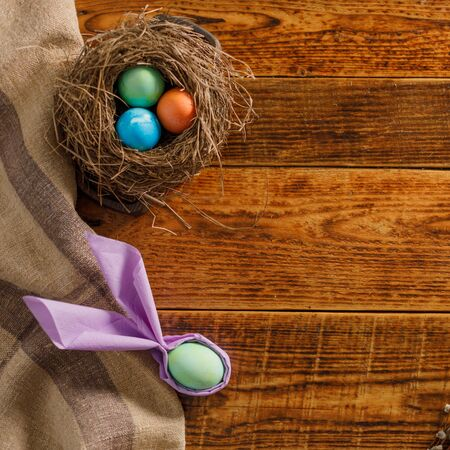 Still life of easter eggs in a bird's nest on a wooden background. Rustic. Easter celebration concept. Copy space. Flat lay