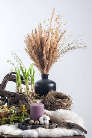 On a table a still life of dried flowers of willow twigs and eggs, a sweet table for the holiday. Easter decoration. Easter holiday concept. Close-up. Stock Photo