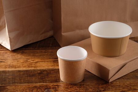 Street fast food paper cups, plates and containers. Eco-friendly food packaging on wooden background. Copy space. Carering of nature and recycling concept. Stock Photo