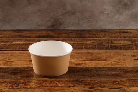 Big brown paper plate isolated on wooden background. Eco-friendly disposable food packaging. Preserving nature and recycling concept.Copy space.