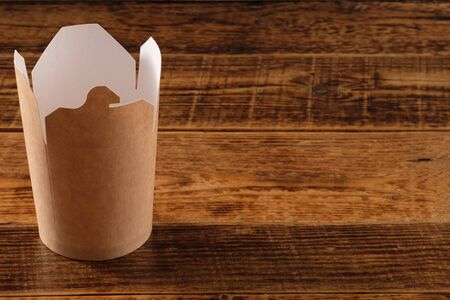 Big brown paper container isolated on wooden background. Eco-friendly disposable food packaging. Preserving nature and recycling concept.