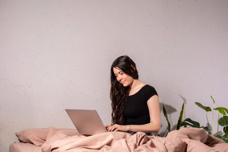 The concept of social distance and isolation. Work from home remotely over the Internet. A young woman works at home on a computer.