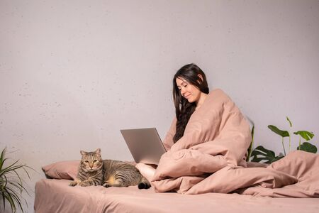 The concept of social distance and isolation. Work from home remotely over the Internet. A young woman works at home on a computer and a cat is next to her. Quarantine. Copy space. Foto de archivo